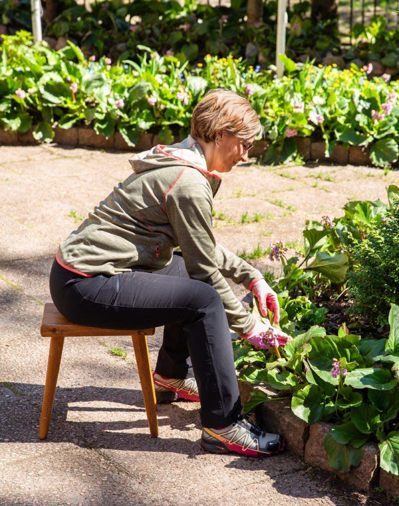 Nainen istuu penkillä ja siistii kukkapenkkiä.