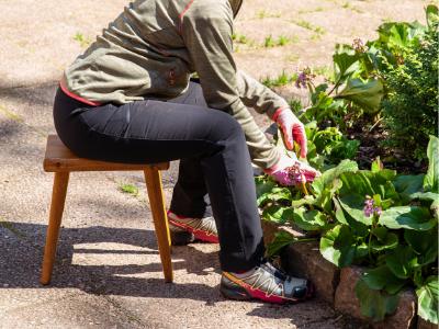 henkilö istuu jakkaralla kukkamaan edessä ja siistii kukkamaata