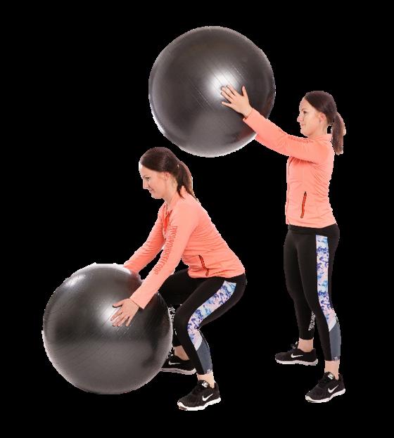 Nainen nostaa jumppapallon lattialta suorille käsille eteen yläviistoon.