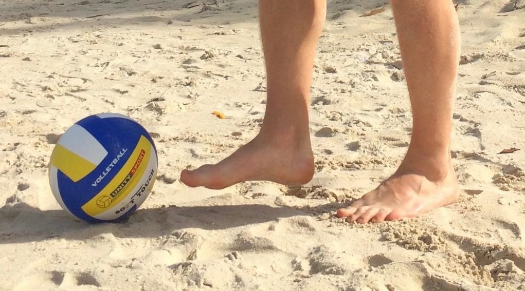 Mies potkii palloa hiekassa.