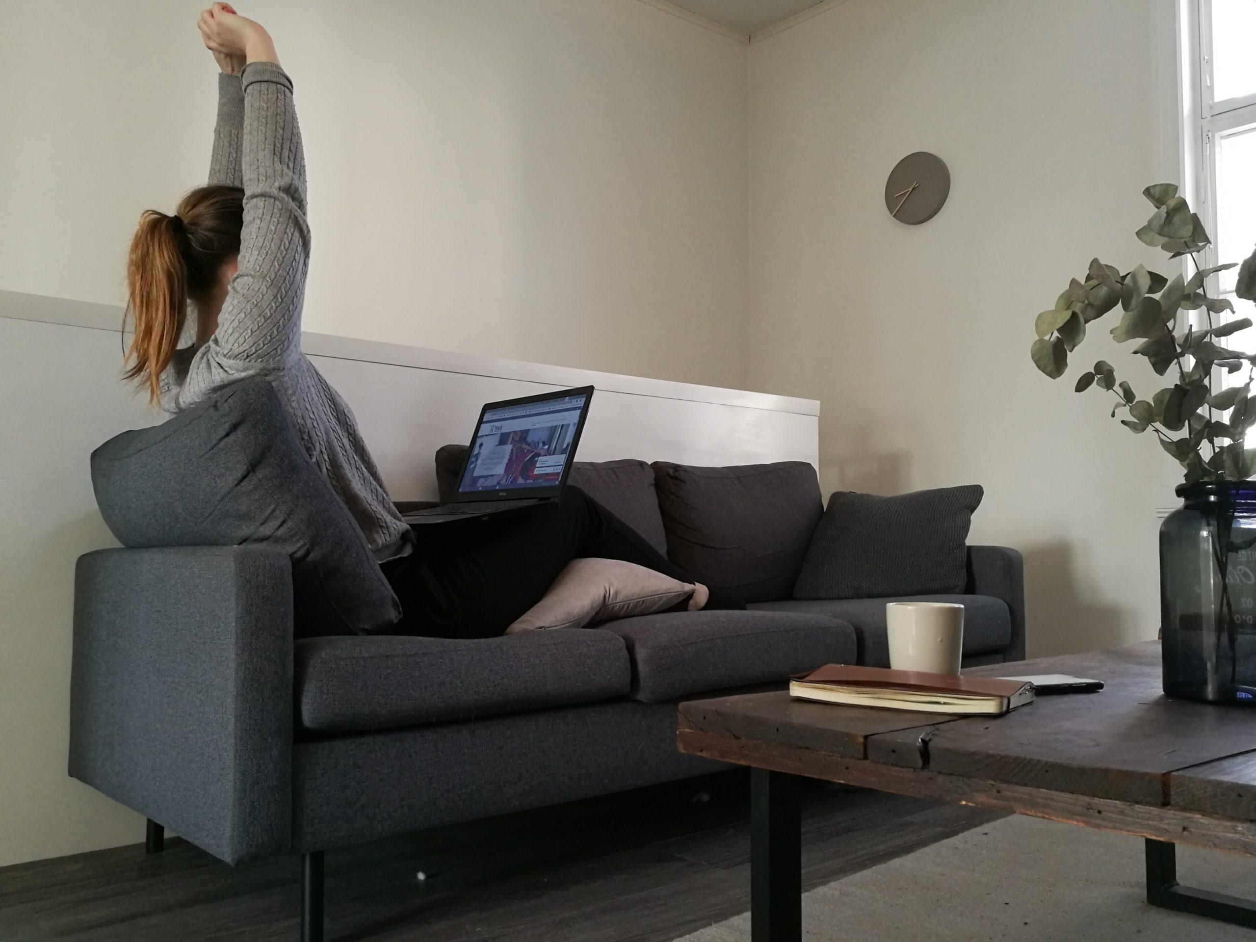 Nainen istuu sohvalla ja venyttää käsillä kohti kattoa.